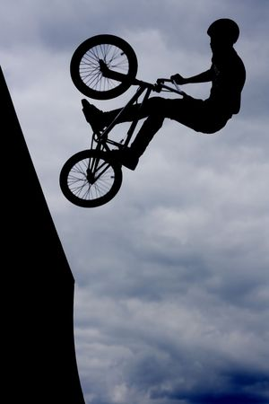 Silhouetted biker boy doing stunts photo