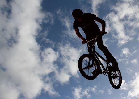 Silhouetted biker boy doing stunts photo