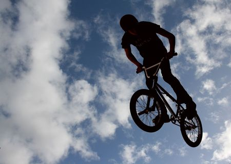 Silhouetted biker boy doing stunts Stock Photo