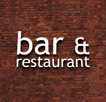 Bar & restaurant sign set on a very old red brick wall Stock Photo