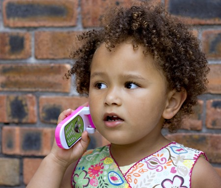 Young black baby girl talking on a toy cell phone Stock Photo