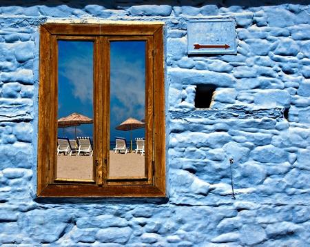 Looking through old wooden window towards blue sky beach photo