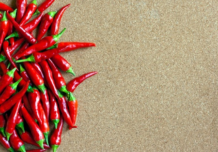 red chilly: Ripe red chillies on cork board Stock Photo