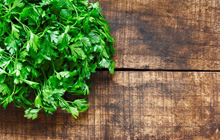 Fresh curly leaf parsley on rustic wooden background Stock Photo