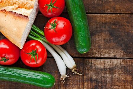 Tomatoes, cucumber, bread and spring onions on old wooden table photo