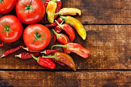 Assortment of chilli peppers and tomato on a rustic wooden table Stock Photo