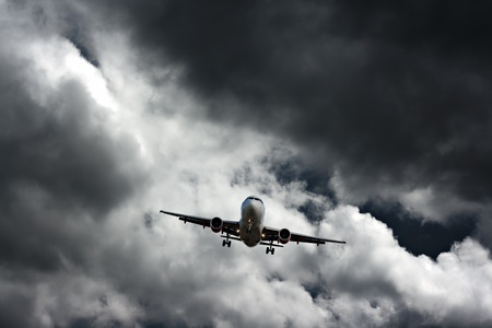 landing light: Passenger plane on final approach, against a stormy sky