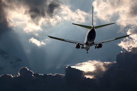Passenger jet landing at airport, against a stormy sky