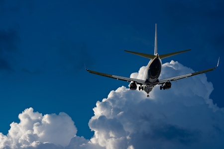 Passenger jet landing against a blue sky with white fluffy clouds photo