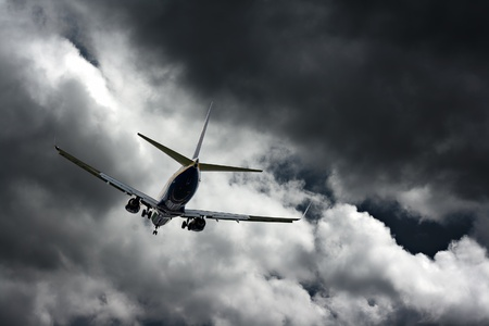 Passenger jet landing at airport, against a stormy sky  photo