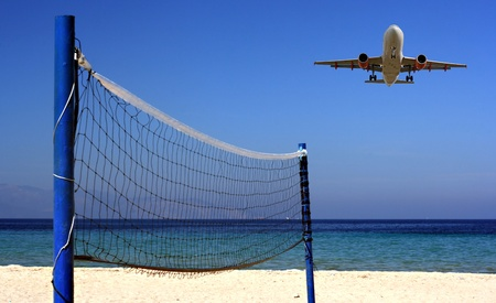 Jet flying over Volleyball net on an empty beach photo