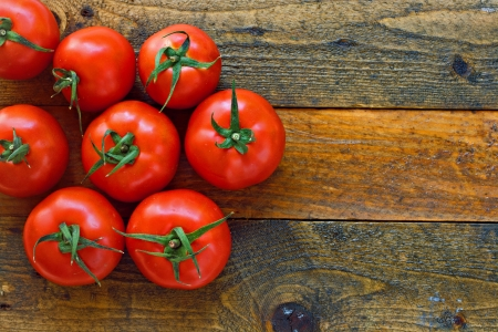 Fresh ripe tomatoes on a rustic wooden table Stock Photo