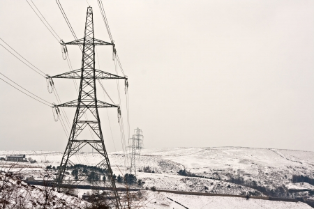 north yorkshire: Electricity pylons on snow covered Yorkshire moors Stock Photo