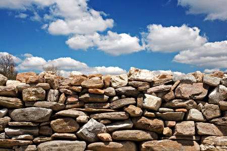 dry stone: Dry stone wall against a blue sky with clouds