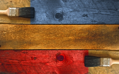 Paintbrushes staining a piece of timber blue and red