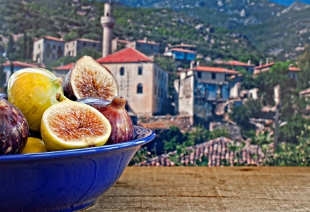 Bowl of fresh figs on rustic wooden table against village background