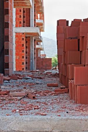 ocas: Pila de ladrillos rojos en una obra de construcción desordenada
