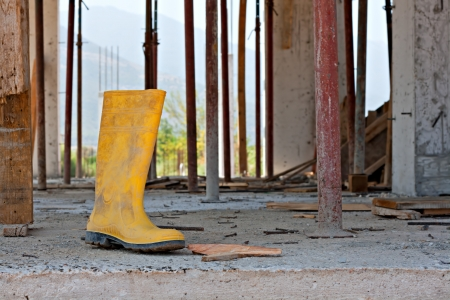 scuffed: Construction workers yellow safety boot, with nails on building site concrete floor Stock Photo