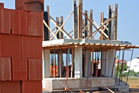 paredes de ladrillos: Pila de ladrillos rojos en una obra de construcción Foto de archivo