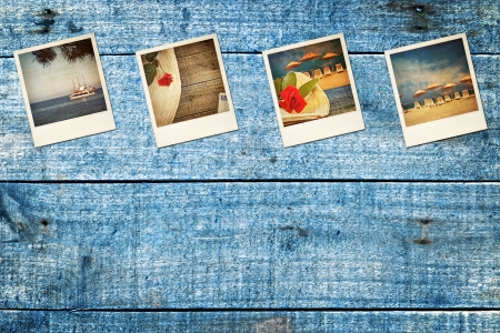 Old worn vacation polaroid pictures, on blue wooden decking Stock Photo