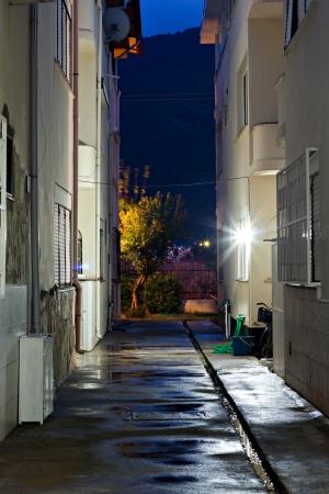 building security: Dark empty back alleyway after the rain