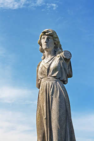 Female weathered statue in ancient graveyard Stock Photo