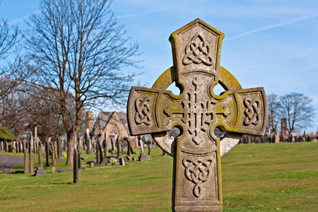 graveyard: A cross in an ancient graveyard with tombstones in the background