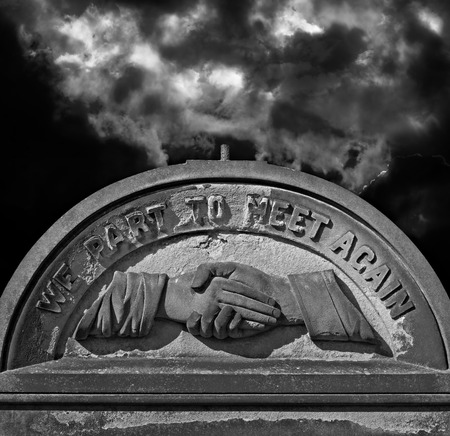 atmospheric: Spooky old weathered cemetery headstone against stormy atmospheric sky Stock Photo