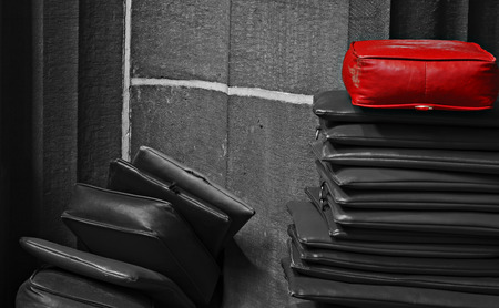 dissident: Red leather cushion on top of a stack of monochrome cushions