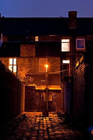 city alley: Dark inner city cobblestoned back alley with streetlight at night