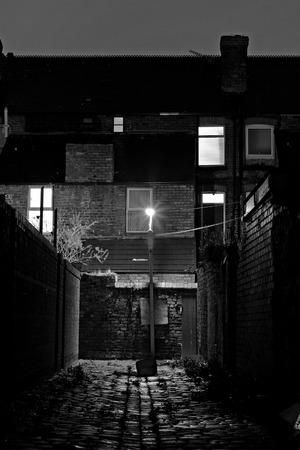 Dark inner city cobblestoned back alley with streetlight at night