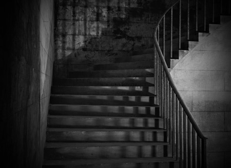 Spooky old stone interior staircase with rusty handrail photo