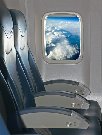 vacation destination: Seating and window inside an aircraft with view of blue sky and clouds