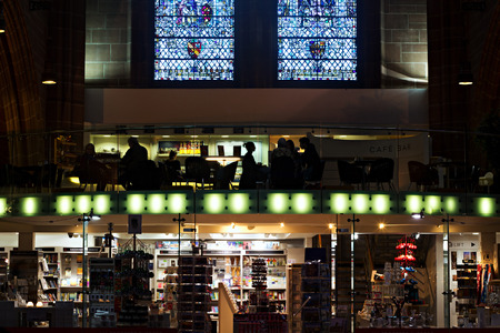 whilst: People in silhouette whilst having coffee inside Liverpool Anglican Cathedral Editorial