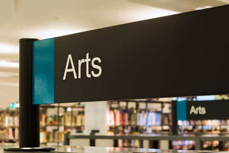 reference book: Arts section sign inside a modern public library