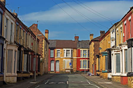 renovate old building facade: A street of boarded up derelict houses awaiting regeneration in Liverpool UK