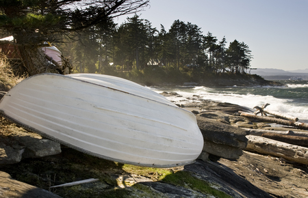 Small overturned rowboat stored on rocky shoreline, Gabriola Island, BC, Canada.