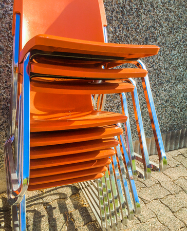 Stack of orange plastic modern chairs outside.