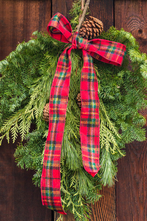 Rustic red and green flannel bow on Christmas wreath.