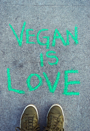 Words Vegan Is Love in green chalk lettering on cement sidewalk. Stock Photo