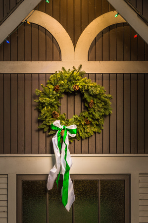 Natural evergreen Christmas wreath on side of old building.