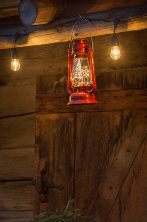 Red metal storm lantern hung outside rustic log cabin. Stock Photo - 115775777