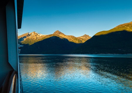 Early morning sunrise light on mountains, from outdoor promenade deck of cruise ship, Taiya Inlet, Skagway, Alaska, USA.