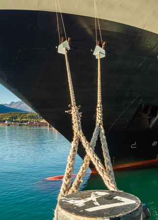 Mooring lines with rat guards extending from bow of cruise ship, tied to bollard at dock , Skagway Alaska, USA. Stock Photo