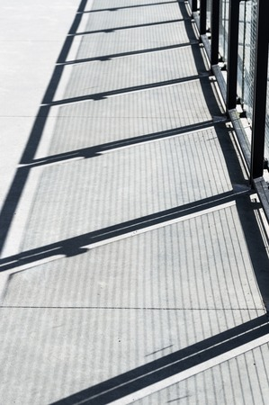 Diagonal shadows on cement walkway from metal and glass panel barrier. Imagens