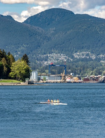 Vancouver, British Columbia, - May 5, 2019:  Brightly dressed scull rowing group in Coal Harbour. 報道画像