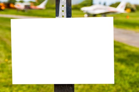 Blank white sign for copy hung on post at small plane air field.