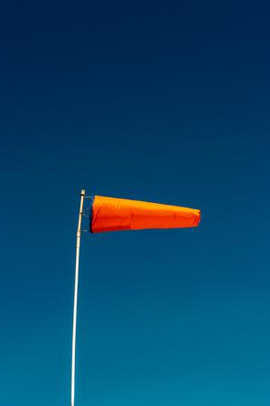 Horizontally flying orange windsock and clear dark blue sky. Stock Photo