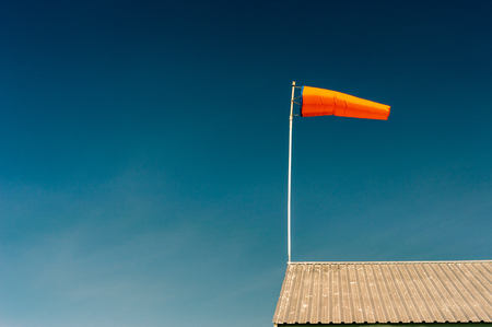 Horizontally flying orange windsock on metal rooftop and clear dark blue sky.