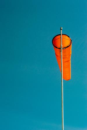 Downward angled plain orange windsock against a clear blue sky. Stock Photo